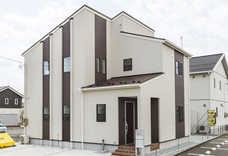 白とブラウンの外壁が印象的なモダン住宅 プライベート空間を配慮の写真1